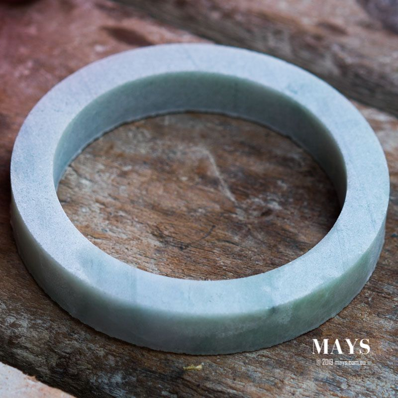 A successful drilling process yields a perfectly round rough jade bangle.