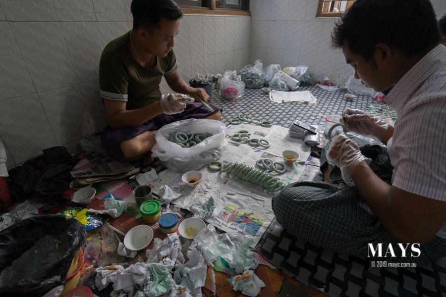 Workers wearing plastic gloves (like the ones used in food handling) to wipe concentrated dyes onto the entire surface of the jade bangles.