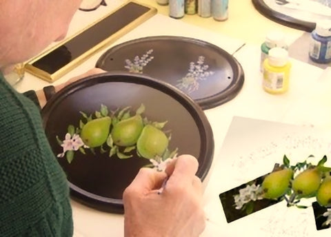 Sign artist hand painting a house plaque with a pears and blossom design