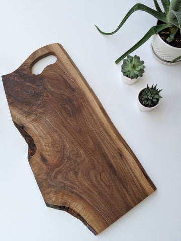 Walnut charcuterie board with grip handle with white background.  Succulents in white pots in the background.