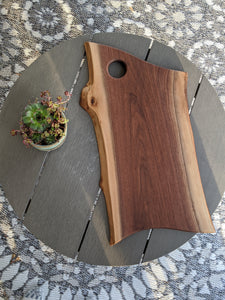 walnut live edge charcuterie board with hole for hanging. Cheese board resting on grey round table with succulents in a blue pot to the side.