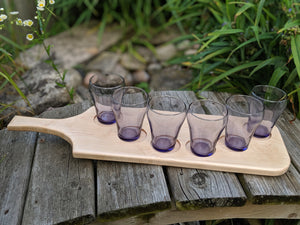 Maple beer flight with six purple beer glasses. Glasses arranged in an arc.