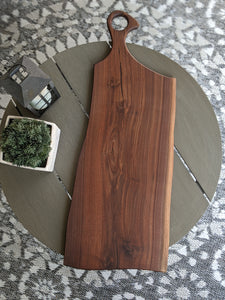 Dark walnut charcuterie board with goose neck handle. Charcoal epoxy accent.