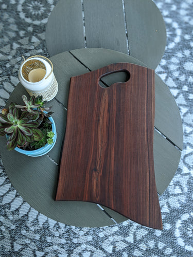 Dark walnut charcuterie board with grip handle on grey table. Green succulants in blue pot to the side.