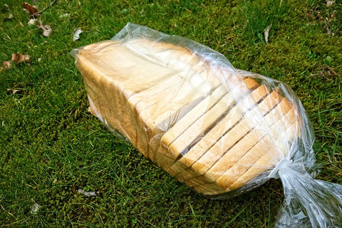 image of a loaf of bread wrapped in a plastic packaging, dumped on grass