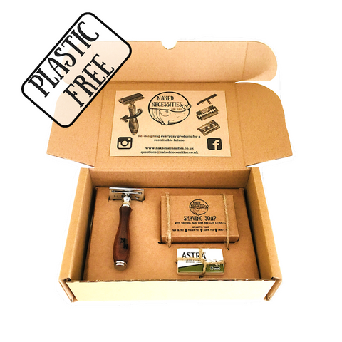 image of an eco-friendly shaving set packaged in a cardboard box, the set contains a razor, blades, and a bar of shaving soap