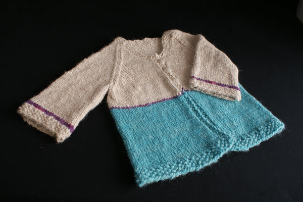 A log sleeved childs cardigan knit in blue and cream with small purple accents