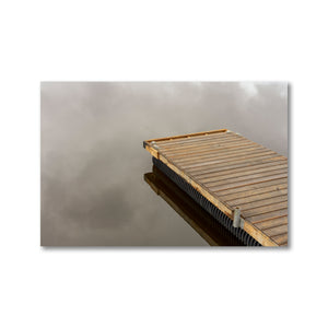 Wood dock on very still reflective water.  Clouds can be seen in cloud reflections.  Framed Art Prints - ZNA Creative