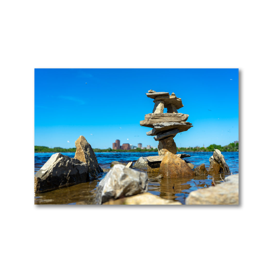 Artistic rock pilings on the Ottawa River with Gatineau in the background on a sunny day with a blue sky.  Framed Art Prints