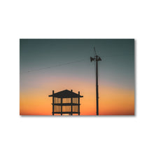 Load image into Gallery viewer, Britannia Beach in Ottawa, Ontario. Silhouette of a beach tower and light post during sunset.  The sun casts a dramatic gradient, slowly changing the sky from a deep blue to a bright and hearty red orange.  Calming artwork for an office or home.
