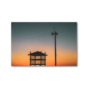 Britannia Beach in Ottawa, Ontario. Silhouette of a beach tower and light post during sunset.  The sun casts a dramatic gradient, slowly changing the sky from a deep blue to a bright and hearty red orange.  Calming artwork for an office or home.