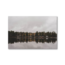 Load image into Gallery viewer, Small grouping of picturesque cottages viewed from across a still lake reflecting the muted sky and landscape like a mirror.  Framed art prints - ZNA Creative