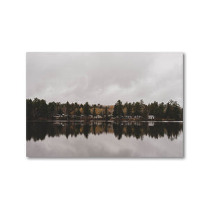 Small grouping of picturesque cottages viewed from across a still lake reflecting the muted sky and landscape like a mirror.  Framed art prints - ZNA Creative