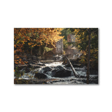 Load image into Gallery viewer, A small historic waterfall creates a golden mist as the water pours over rocks and through the fall leaves colours.  Framed art prints - ZNA Creative