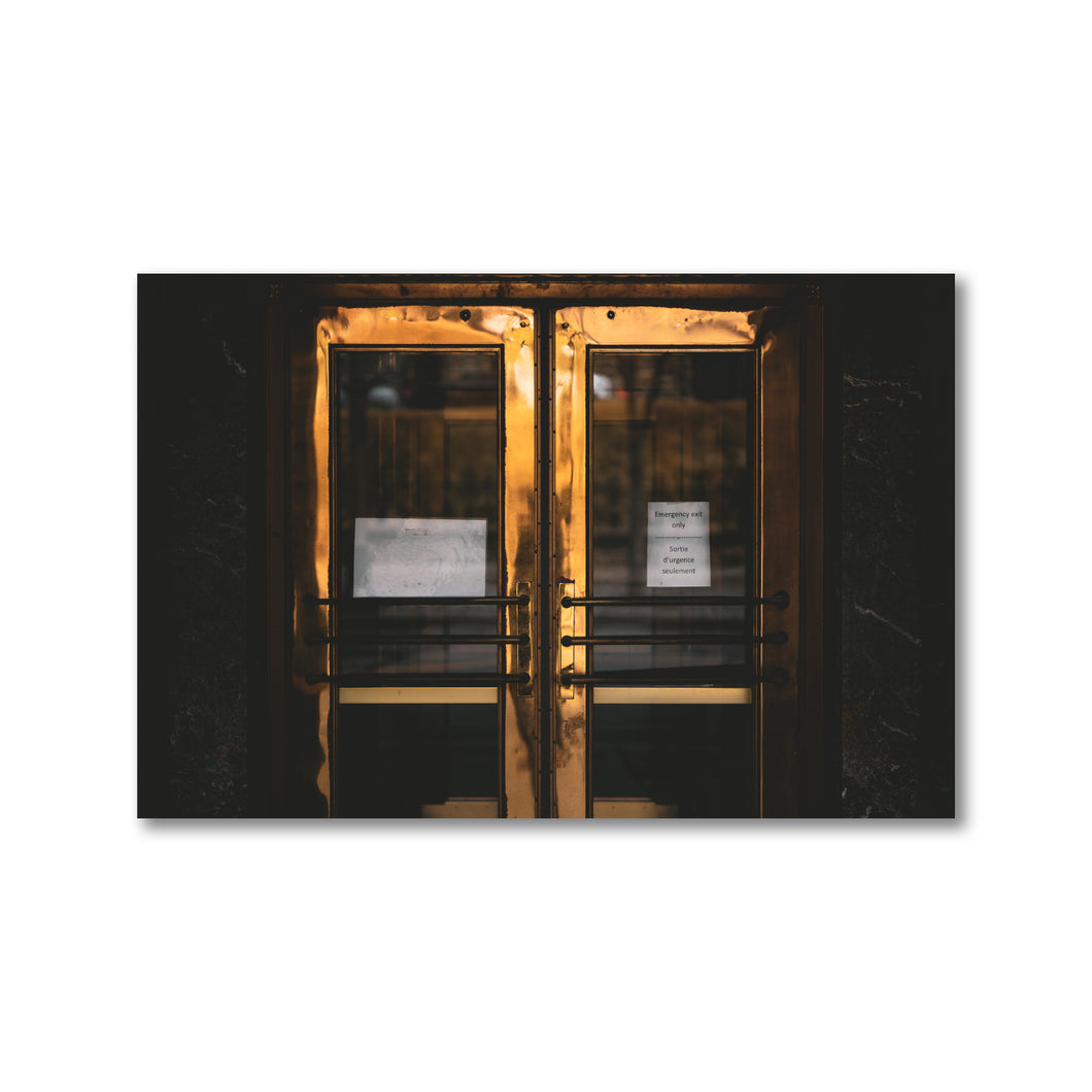 Double doors in a darkened, outdoor entryway.  The doors are made of brass, but have a deep, moody golden glow.  A paper sign can be seen taped to the door with printed text reading