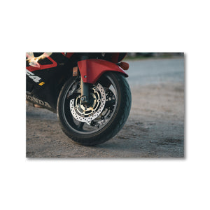 A framed photography print, perfect for any home, office, or garage. A Honda motorcycle tire is pictured, the red paint pops against the contrasted gravel parking lot ground. Framed giclee art prints.