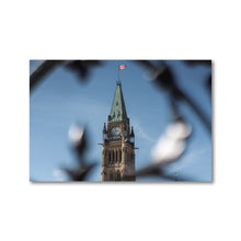 Load image into Gallery viewer, A 12x18 framed print of The Peace Tower of Canada's Parliament, in Ottawa, Ontario.  A light blue sky with wisps of cloud can be seen in the background behind the gothic style tower.  The decorative wrought iron gates can be seen in the foreground, framing the tower and Canadian flag.  Ottawa Canada Framed Prints, ZNA CREATIVE.