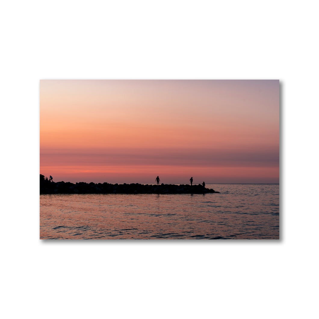 Three sunset silhouettes of people playing on rocks break wall a distance out on Georgian Bay, Ontario.  Framed sunset art prints 12x18 - ZNA Creative