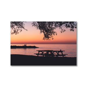 Sunset on Geogrian Bay's Northwinds Beach. The silhouettes of two people can be seen on the rock wall out in the water, and the gentle silhouette of two picnic tables can also be seen, cast against the dramatic South Georgian Bay sunset.
