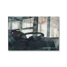 Load image into Gallery viewer, 12x18 Framed Print.  View of an old blue school bus steering wheel, as seen from outside looking in.  The sliding bus widows are visible in the background, and the reflection of the windshield is visible in the frame.  This photograph has a very moody tone, and is suitable for any home or office decor.  ZNA Creative