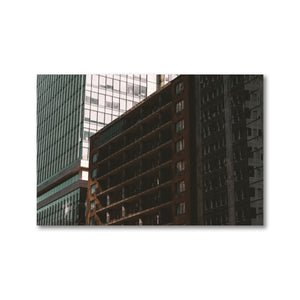A 12x18 framed print of a bright building casting a shadow upon an apartment building beneath it.  This moody photograph was taken downtown Ottawa, Canada.  The shadowed apartment has an 80s feel, with red brick and concrete balconies; while the bright tower next to it is modern, with light blue curtain wall glass.  Framed Office Art Prints.  ZNA Creative