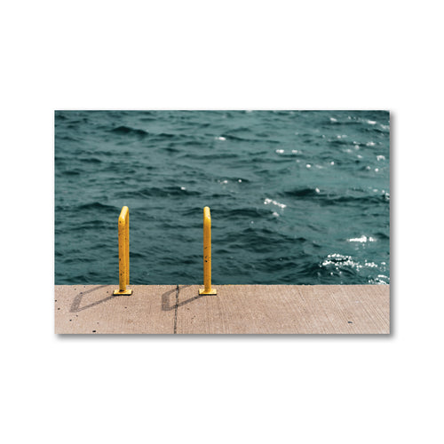 A framed art print of a pier. A yellow ladder runs from the concrete of the pier into the deep blue waters of Georgian Bay's Collingwood Harbour