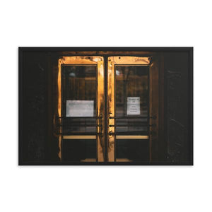 "Double doors in a darkened, outdoor entryway.  The doors are made of brass, but have a deep, moody golden glow.  A paper sign can be seen taped to the door with printed text reading ""Emergency Exit Only"".  Perfect wall decor for any home or office. This framed print has a black alder frame, and is 12x18 inches."