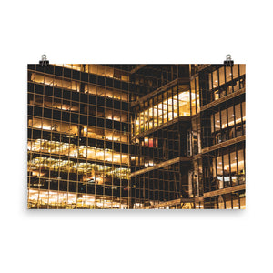 Yellow office lights at night visible through the glass windows of a downtown skyscraper.  This fine art photography poster print is available in various sizes and has FREE shipping to the USA | ZNA Creative