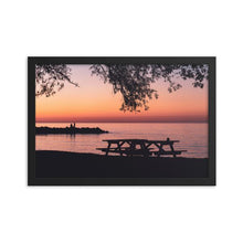 Load image into Gallery viewer, Sunset on Geogrian Bay's Northwinds Beach. The silhouettes of two people can be seen on the rock wall out in the water, and the gentle silhouette of two picnic tables can also be seen, cast against the dramatic South Georgian Bay sunset.