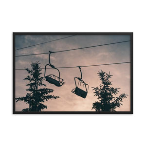The silhouettes of two chairlifts between two Canadian pine trees are cast against a dramatic sunset with wisps of clouds and sky.  Taken in The Blue Mountains, Ontario at Blue Mountain Resort