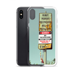 A stylish iPhone case featuring an abandoned no trespassing sign, with some type of old, thrown away apparel hanging from the sign post.  Trending iPhone cases