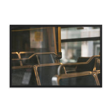 Load image into Gallery viewer, A photograph of empty seats on an OC Transpo bus in Ottawa, Canada.  The blue, ridged fabric on the seats can be seen through the tasteful reflection of the outer bus window.  Framed Print shown with a black alder frame, in the size of 12x18 inches.