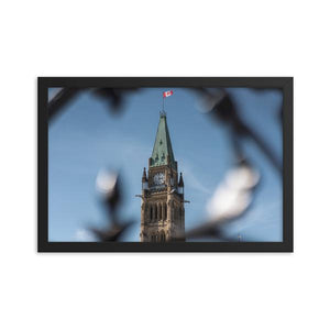 A 12x18 framed print of The Peace Tower of Canada's Parliament, in Ottawa, Ontario.  A light blue sky with wisps of cloud can be seen in the background behind the gothic style tower.  The decorative wrought iron gates can be seen in the foreground, framing the tower and Canadian flag.  Ottawa Canada Framed Prints, ZNA CREATIVE.