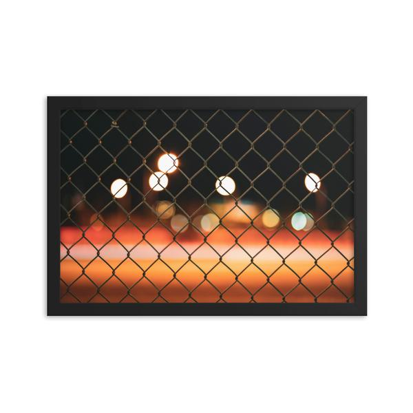 Warm tones of orange, red and yellow are wiped across the print in this framed long exposure photography print.  Highway 417's bokeh is pictured through a blurred chain link fence