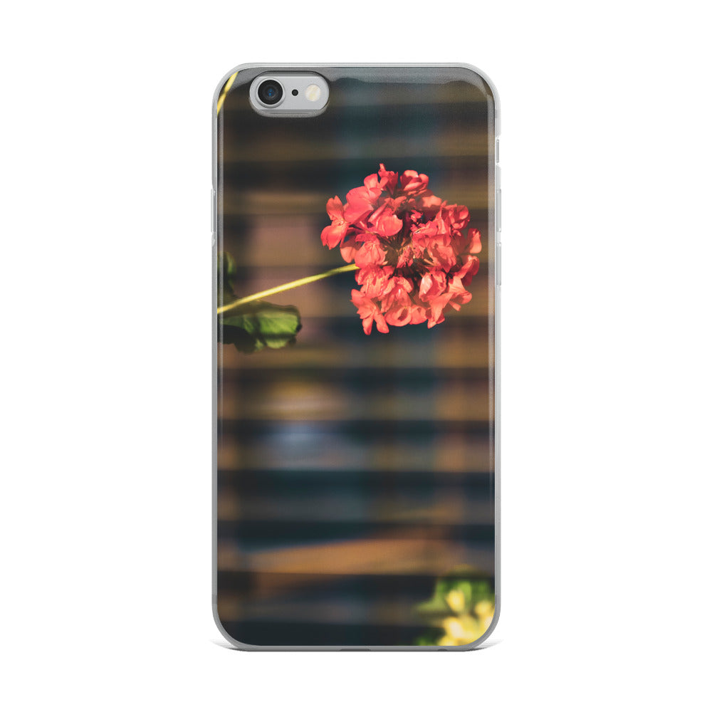 Creative iPhone case with beautiful red/rose flower, as seen through the slight bokeh blur of the horizontal window shades