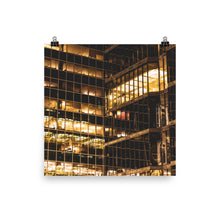 Load image into Gallery viewer, Yellow office lights at night visible through the glass windows of a downtown skyscraper.  This fine art photography poster print is available in various sizes and has FREE shipping to the USA | ZNA Creative