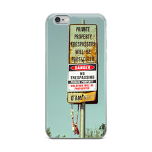 Load image into Gallery viewer, A stylish iPhone case featuring an abandoned no trespassing sign, with some type of old, thrown away apparel hanging from the sign post.  Trending iPhone cases