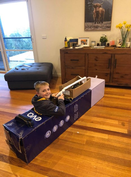 Young boy plafully turns bed in a box into a fighter jet