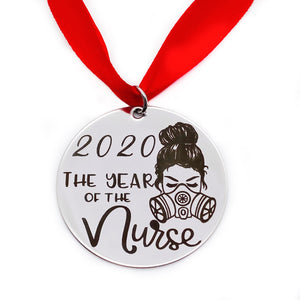 "front view of round silver stainless steel christmas ornament engraved with ""2020 the year of the nurse"" with an image of a female nurse wearing a n95 mask. It hangs from a red ribbon."