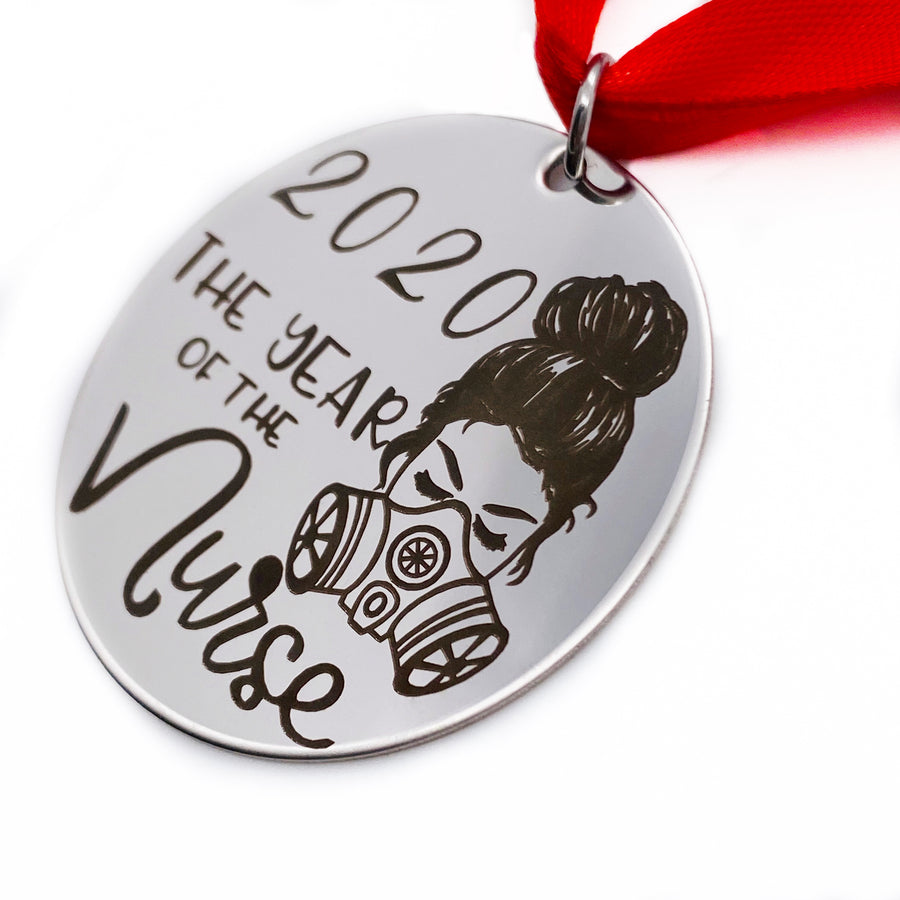 "right side view of round silver stainless steel christmas ornament engraved with ""2020 the year of the nurse"" with an image of a female nurse wearing a n95 mask. It hangs from a red ribbon."