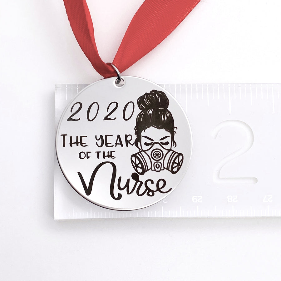"round silver stainless steel christmas ornament engraved with ""2020 the year of the nurse"" with an image of a female nurse wearing a n95 mask. It hangs from a red ribbon. on a ruler showing measurement of 1.5 inches"