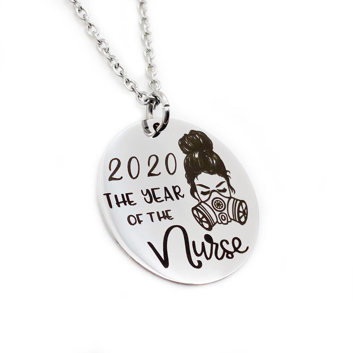 "7/8"" silver stainless steel pendant engraved with an image of a messy bun female nurse wearing a gas mask. The image is accompanied by the phrase ""2020 the year of the nurse"". the charm pendant is attached to a stainless steel silver cable chain with lobster clasp"
