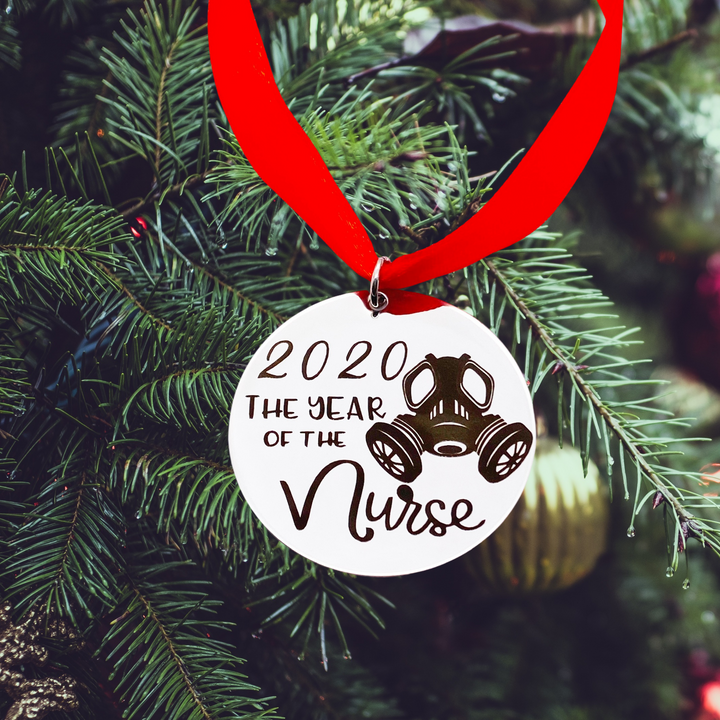 "round silver stainless steel christmas ornament engraved with ""2020 the year of the nurse"" with an image of a gas mask. It hangs from a red ribbon."