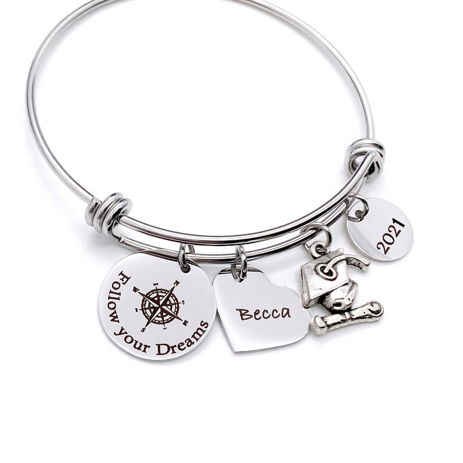 "Silver Stainless Steel Engraved charm bracelet. circle disc engraved with ""Follow your Dreams"" with a compass image. Next is a heart name charm. next is a graduation cap and tassel charm. lastly is a circle charm with the year ""2021"" engraved. All charms are attached to a triple loop stainless steel bangle bracelet"