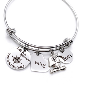 "Silver Stainless Steel Engraved charm bracelet. circle disc engraved with ""life is a journey. you hold the map"" with a compass image. Next is a heart name charm. next is a graduation cap and tassle charm. lastly is a circle charm with the year ""2021"" engraved. All charms are attached to a triple loop stainless steel bangle bracelet"