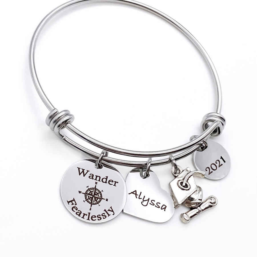 "Silver Stainless Steel Engraved charm bracelet. circle disc engraved with ""Wander Fearlessly"" with a compass image. Next is a heart name charm. next is a graduation cap and tassel charm. lastly is a circle charm with the year ""2021"" engraved. All charms are attached to a triple loop stainless steel bangle bracelet"