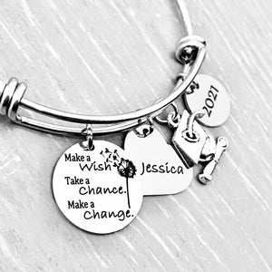 "Silver Stainless Steel Engraved charm bracelet. circle disc engraved with ""Make a wish. Take a chance. make a change"" with a dandelion image. Next is a heart name charm. next is a graduation cap and tassel charm. lastly is a circle charm with the year ""2021"" engraved. All charms are attached to a triple loop stainless steel bangle bracelet"