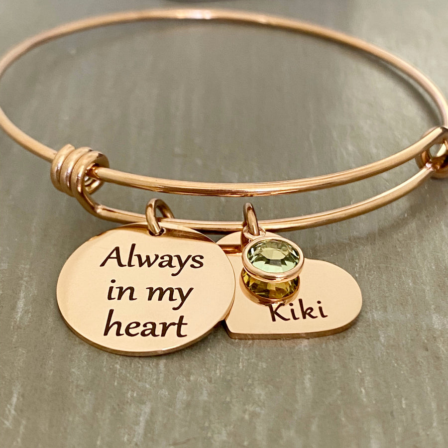 "rose gold triple loop bangle charm bracelet. engraved on a 3/4"" round charm is the verbiage ""always in my heart"". next to that is a 3/4"" heart charm engraved with the name ""kiki"" and a august birthstone on top."