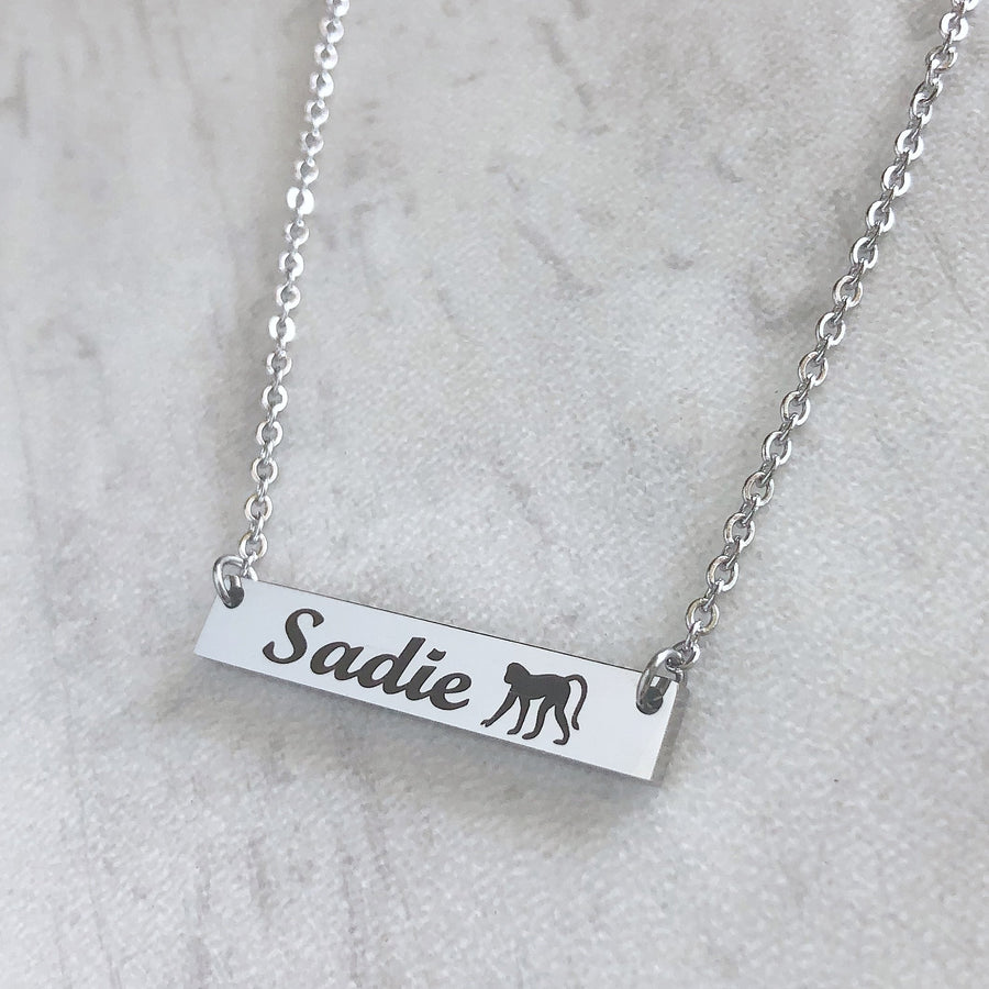 rectangle silver bar necklace with black engraving of the name sadie and a monkey with cable chain