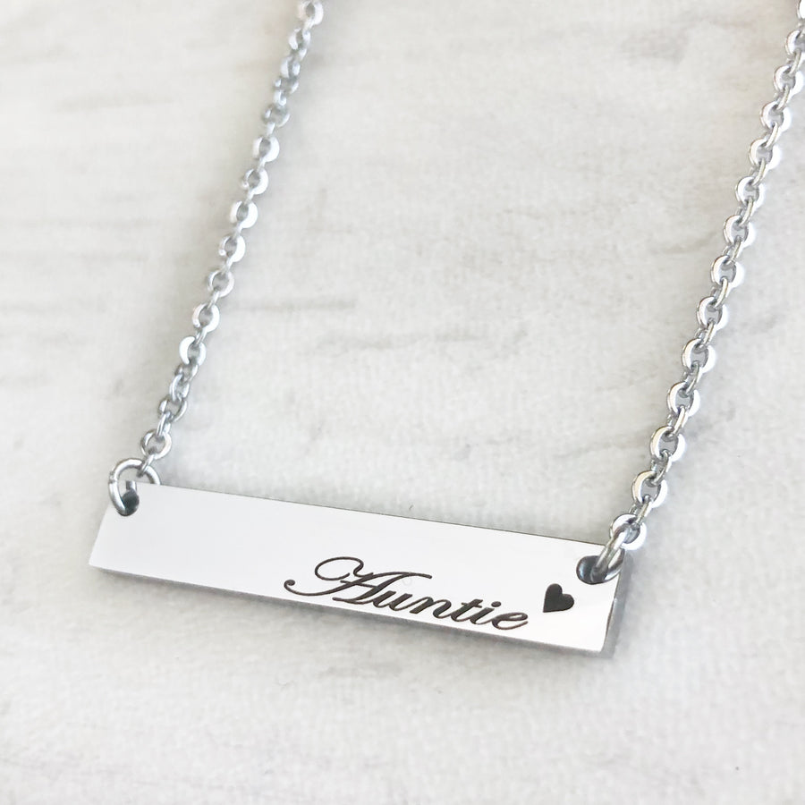 Shiny silver bar necklace engraved with auntie and a heart attached to a cable chain